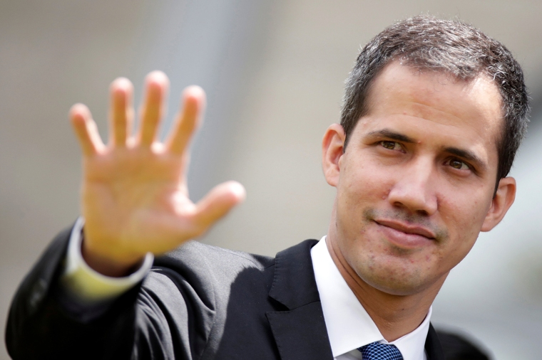 Venezuelan opposition leader Juan Guaido waves after a meeting at the European Union headquarters in Brasilia